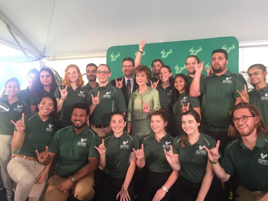 Judy Genshaft and her husband, Steven Greenbaum, are surrounded by students from the USF Honors College in May 2019.