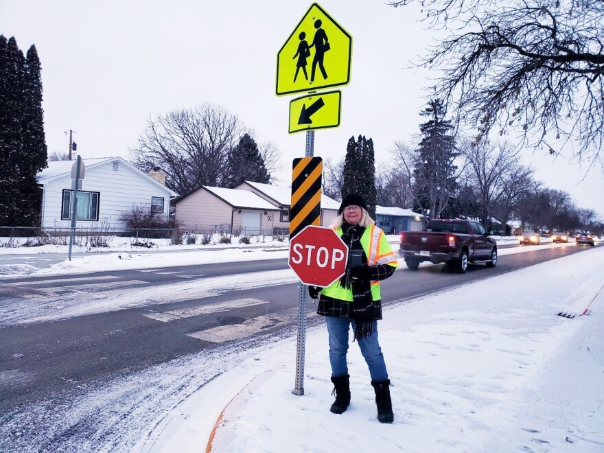 Ethelyn Howard, wearing a reflective yellow vest and holding a stop sign, stands on the sidewalk next to a street crosswalk.