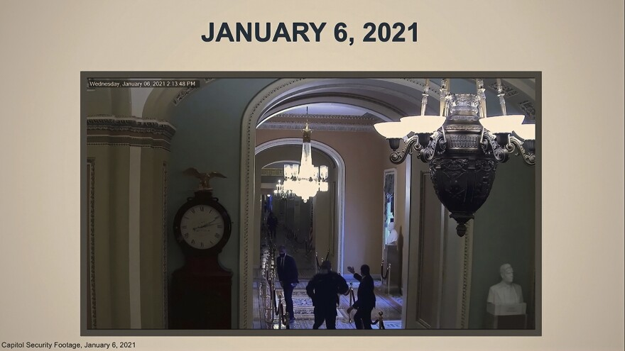 In this image from video, a security video shows U.S. Capitol Police officer Eugene Goodman running past Sen. Mitt Romney, R-Utah (left) and urging him to turn around. Impeachment manager Stacey Plaskett showed the video as evidence the rioters came close to threatening lawmakers.