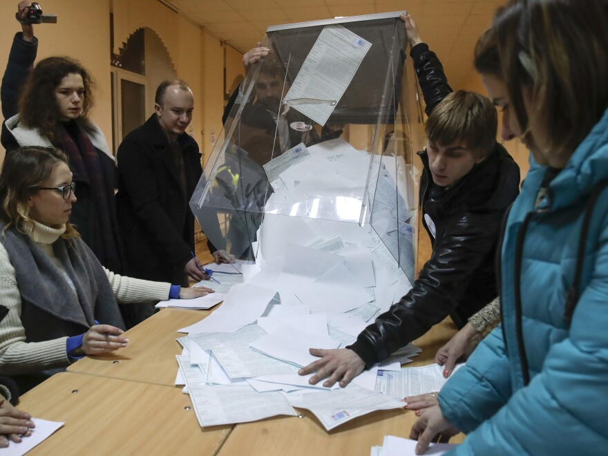 The members of the local election commission open a ballot box for counting at a polling station, during the presidential elections in St.Petersburg, Russia, on Sunday.