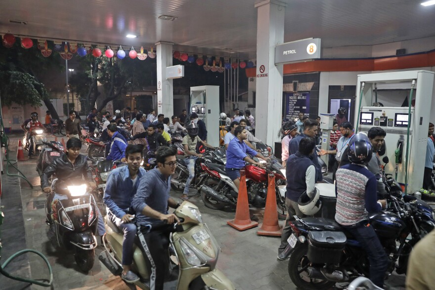Indians crowd a gas station, one of the few places still accepting the high denomination 1,000 and 500 currency notes, in New Delhi.