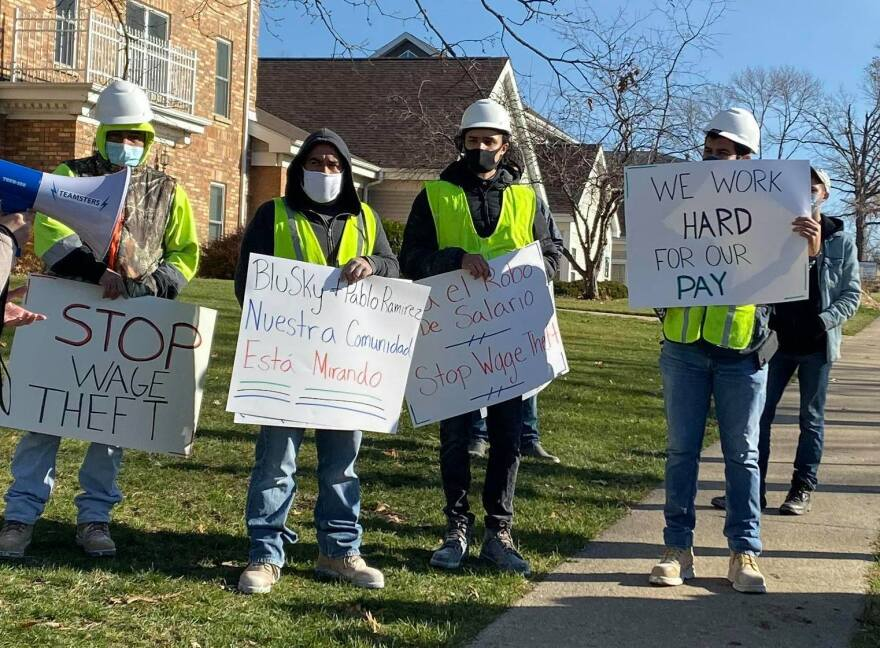 """Four men in neon yellow work vests and face masks hold signs that say """"Stop wage theft, BluSky, Pablo Ramirez, Nuestro comunidad, esta mirando, We work hard for our pay."""""""