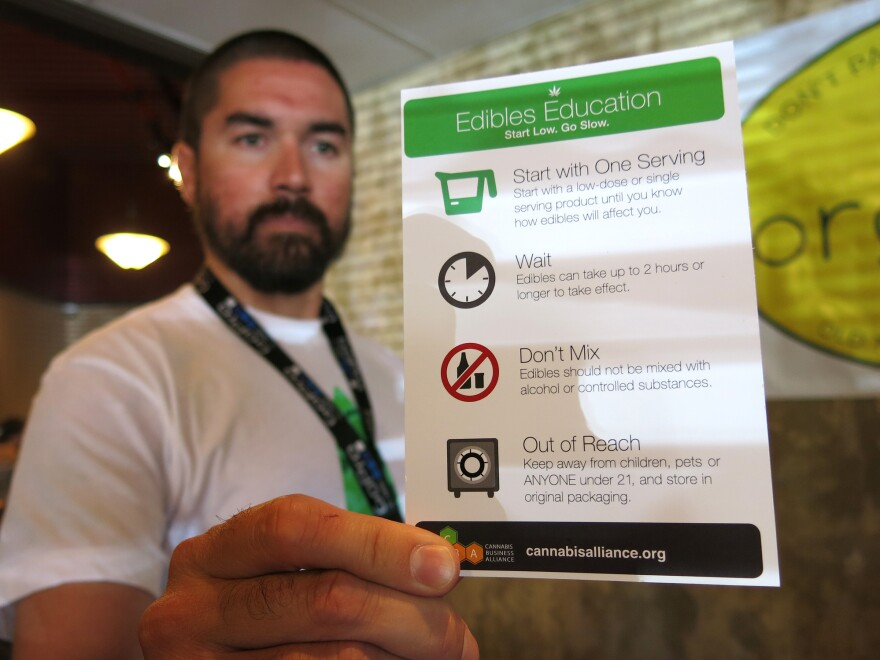 Maka Kalaí, the manager of Organic Alternatives, a recreational and medical marijuana store in Fort Collins, Colo., hands out edibles education cards with each purchase.