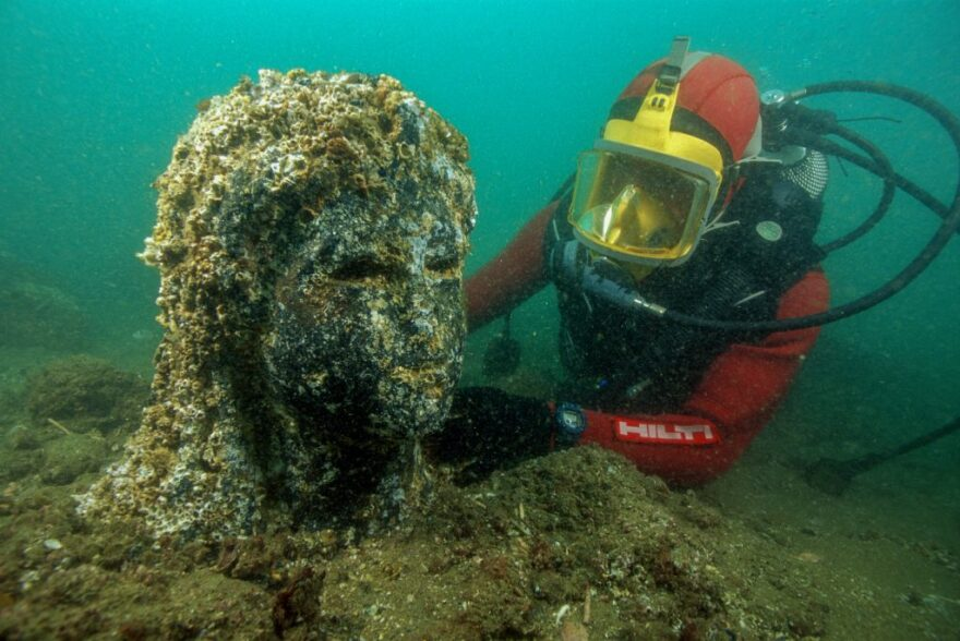 An archaeologist inspects the head still encrusted of a black stone queen on site underwater in Thonis-Heracleion, Egypt; Ptolemaic Period; granodiorite; height: 86 5/8 inches; National Museum, Alexandria (SCA 283), IEASM Excavations