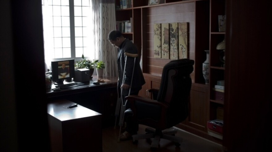 Zhou Wangyan says his leg was broken by interrogators in China's secretive detention center in fall 2012. In January 2014, he still uses crutches to stand.