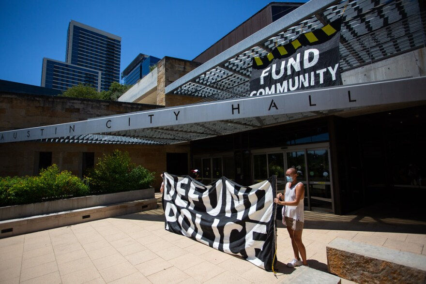 Student protesters hold a sign outside Austin City Hall on Saturday calling for the city to defund police and invest more in the community.