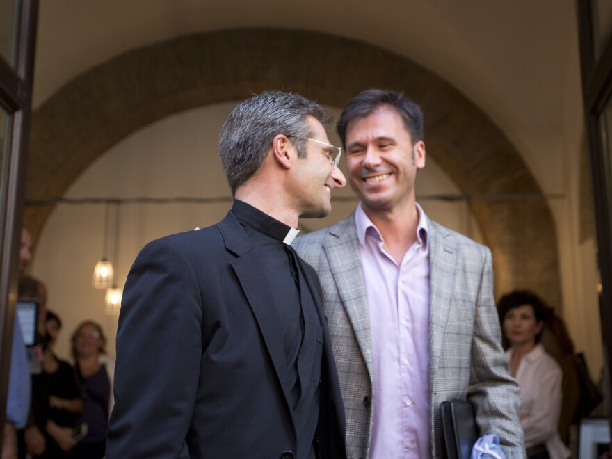Monsignor Krzysztof Charamsa, left, and his partner Eduard, surname not given, leave a restaurant after a news conference in downtown Rome, on Saturday. The Vatican on Saturday fired Charamsa who came out as gay on the eve of a big meeting of the world's bishops to discuss church outreach to gays, divorcees and more traditional Catholic families.