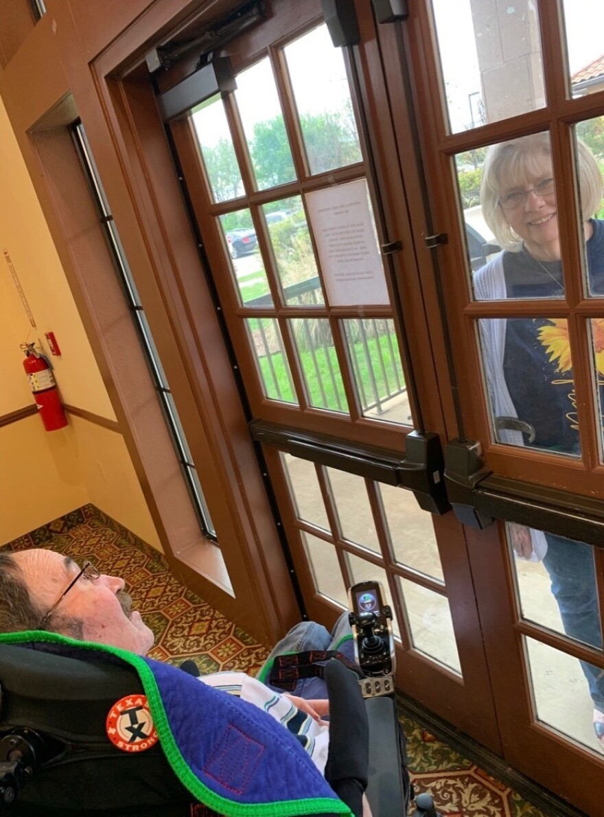 Luann Thibodeau visits her husband at his nursing home, with a glass door between them.