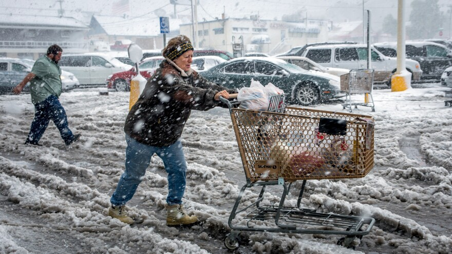 As snow fell in Rapid City, S.D., Friday Brenda Nolting took groceries to her car. An early snow storm swept through Wyoming and western South Dakota, dropping more than two fee of snow in some areas.