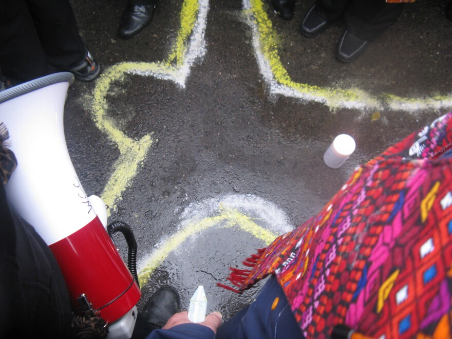 Demonstrators sketched a chalk outline of a body on the pavement of the Ferguson Police Station on October 13.
