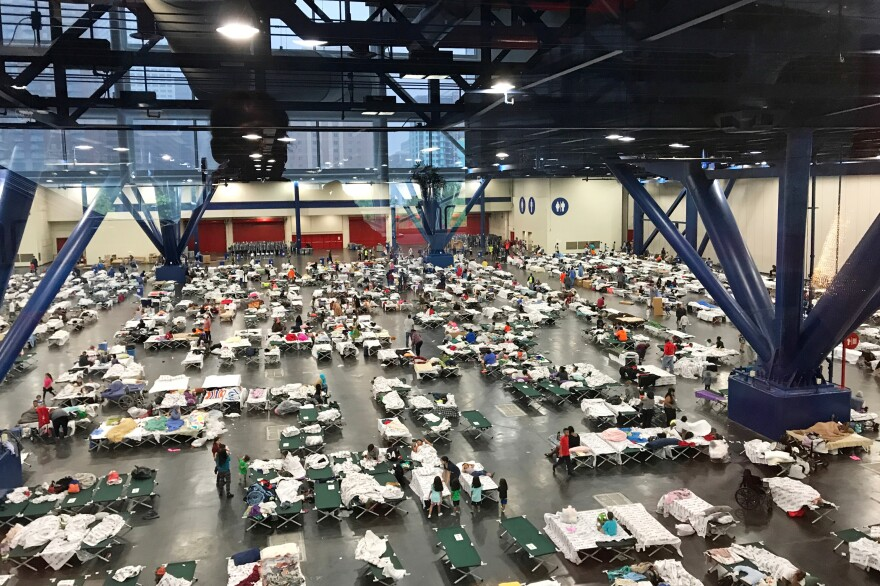 People gather around cots inside the George R. Brown Convention Center in Houston as they take shelter from the flooding on Monday.