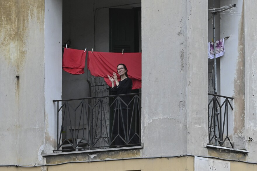From their windows and balconies in Rome, Italians form a flash mob to cheer and make music for Italian health workers on March 14.