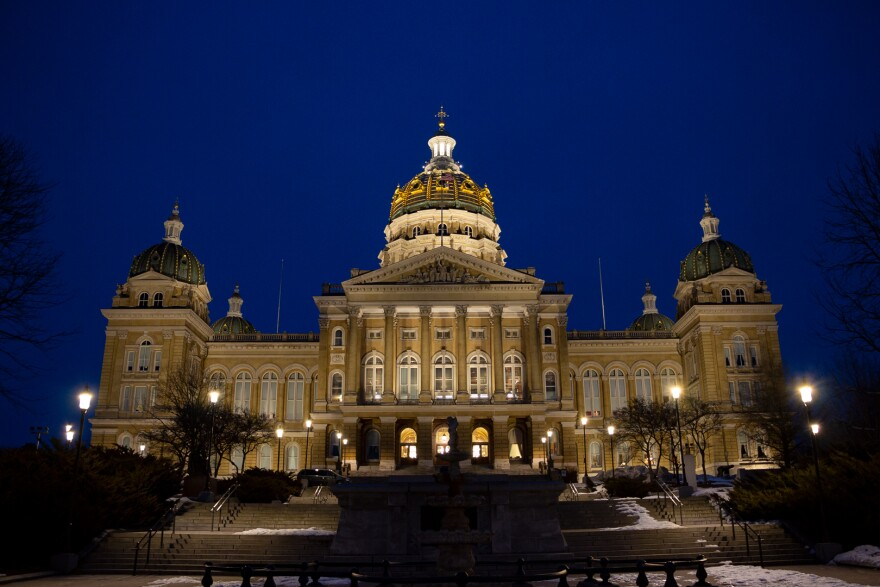 The Iowa Capitol is lit up in front of a dark blue night sky.
