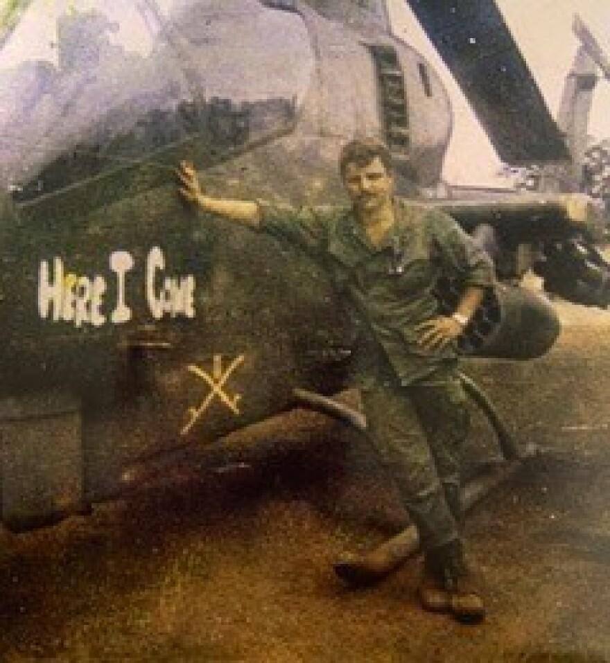Veteran Harry Stapleton next to a helicopter in the Vietnam War.