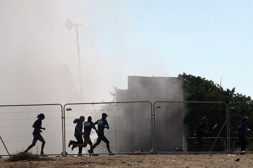Israelis run for cover seconds after the Iron Dome system, shown in the background, fired an anti-rocket missile near the southern city of Ashkelon on Aug. 26. Israel developed the Iron Dome system itself and has used it to defend against Palestinian rockets from the Gaza Strip.