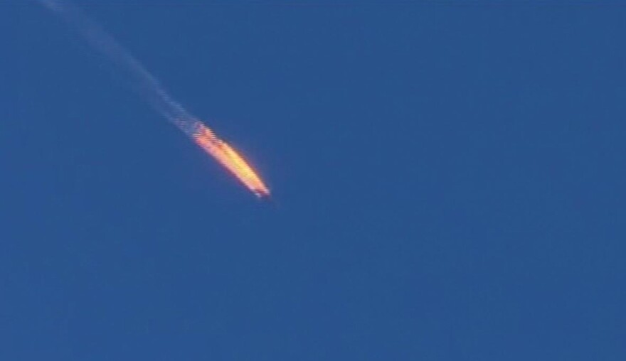 This frame grab from video by Haberturk TV shows a Russian warplane on fire before crashing on a hill as seen from Hatay province, Turkey, on Tuesday.