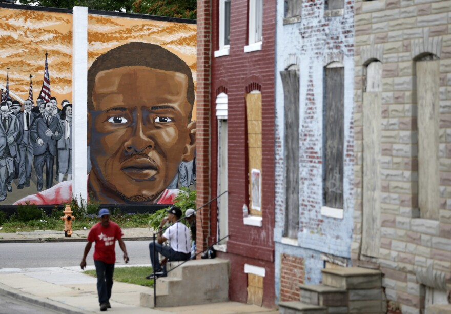 People walk by a mural depicting Freddie Gray in Baltimore on June 23, at the intersection where Gray was arrested in 2015. Prosecutors in Baltimore have dropped all remaining charges against police officers related to Gray's death while in police custody.