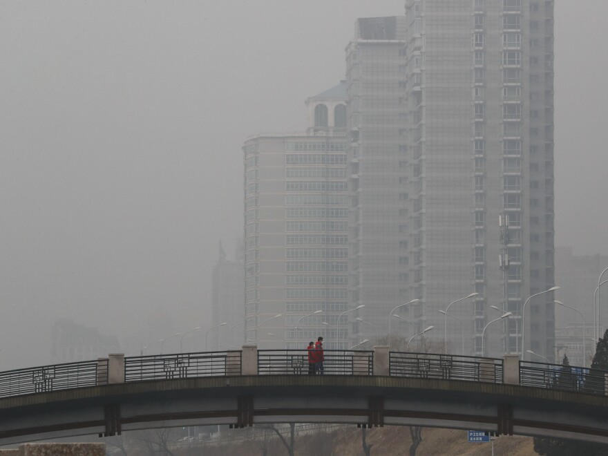Chinese men wearing masks walk on a bridge near a building shrouded by fog and pollution in Beijing on Jan. 5. China has long faced some of the worst air pollution in the world, blamed on its reliance on coal and older, less efficient cars. Inadequate controls on industry and lax enforcement of standards have worsened the problem.