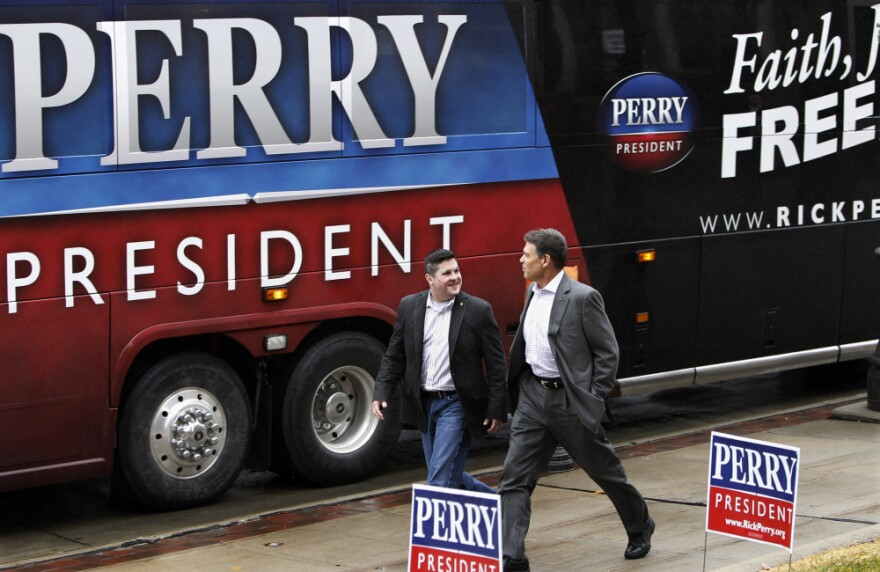 Republican presidential candidate Rick Perry walks with former Marine officer Dan Moran during a campaign stop Wednesday in Council Bluffs, Iowa.