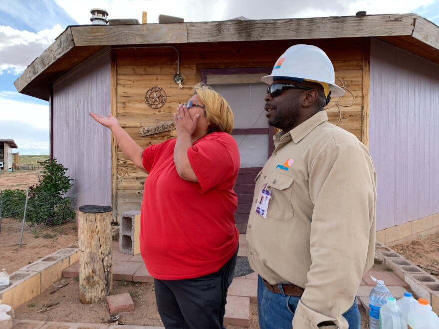 Brian Cooper of PNM Electric in New Mexico tells Neda Billie that the company would like to give her family a refrigerator. Several crews from utilities around the country are volunteering their time to connect people like the Billies to the power grid.