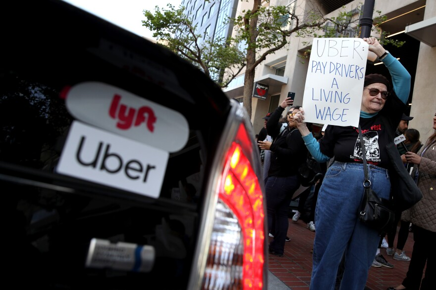 A supporter of ride-hail drivers holds a sign during a protest in front of Uber headquarters on May 8 in San Francisco. A new law in California aims to change how gig economy and other contract workers are classified.