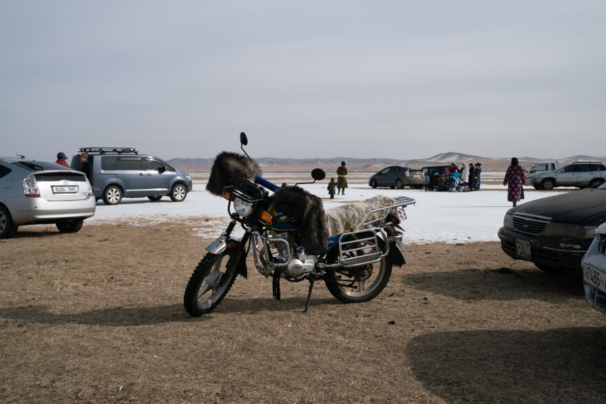 Cars and motorcycles draped with fur line the banks of the Tamir as players gather for the season's final ice shooting competition in early March.