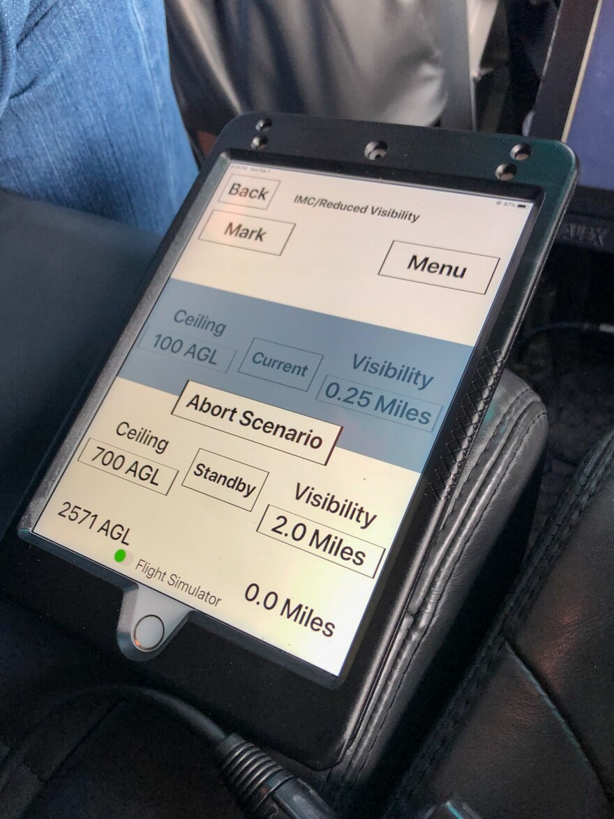This iPad controls what the pilot 'sees' during the actual flight. In this case, his vision was obscured by low clouds but it was set to improve slightly as he continued on this training mission.
