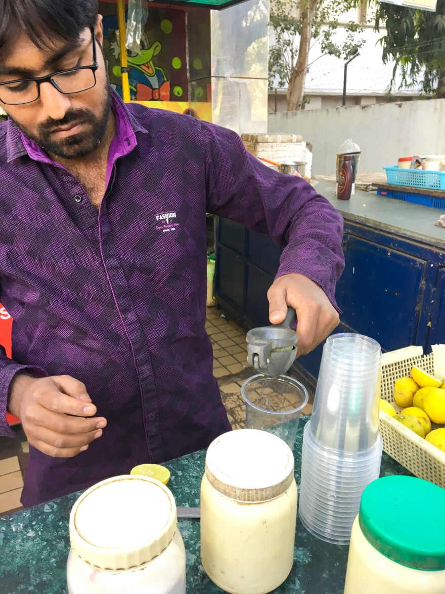A soda vendor in Mumbai squeezes fresh lemons for a <em>nimbu </em>soda. The plastic jars in front of him contain spice mixes for different flavors.