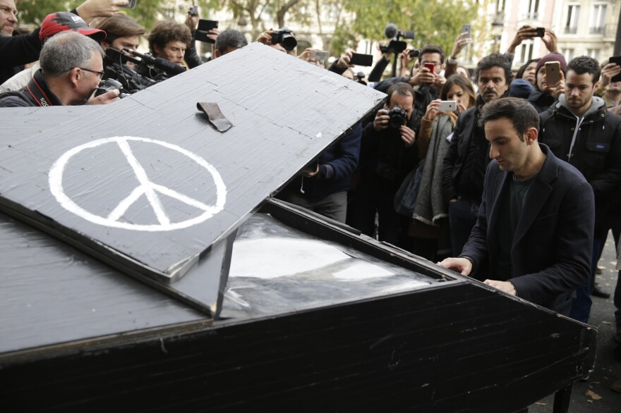 A man plays piano near the Bataclan theater in Paris on Saturday, the day after a series of attacks on the city resulted in the deaths of at least 120 individuals. At least 80 people died inside the Bataclan.