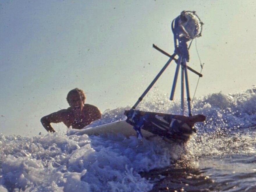 Bruce Brown, seen in 1963, attempts to balance a mounted camera on his board while catching a wave. The man behind the seminal 1966 surfing documentary <em>The Endless Summer</em> died Sunday at his home in Santa Barbara, Calif., at the age of 80.