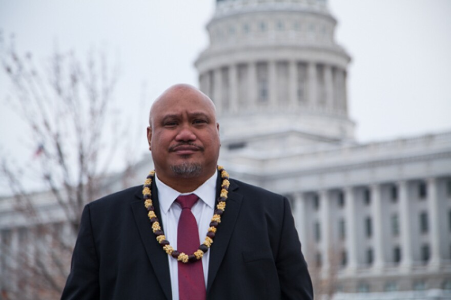 Photo of a Samoan man in a suit and a lei in front of government building.
