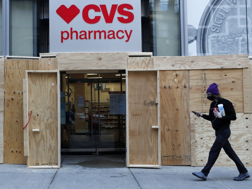 A man walks past a boarded-up CVS Pharmacy store in Boston on Oct. 31, 2020.