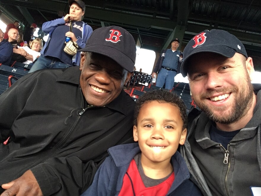 Calvin Hennick (right) attends a Red Sox game with his son, Nile, and his father-in-law, Guy Mont-Louis, at Boston's Fenway Park. Hennick reported a white fan who he said made a racist remark about a Kenyan woman who sang the national anthem.
