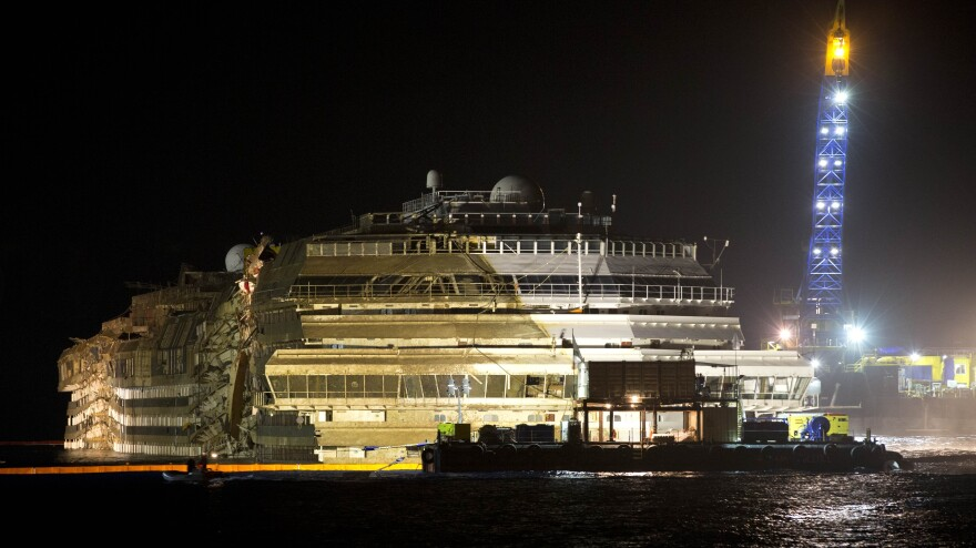 """The Costa Concordia is seen after it was lifted upright on the Tuscan Island of Giglio, Italy, early Tuesday morning. Officials declared the results of the 19-hour operation """"perfect."""""""