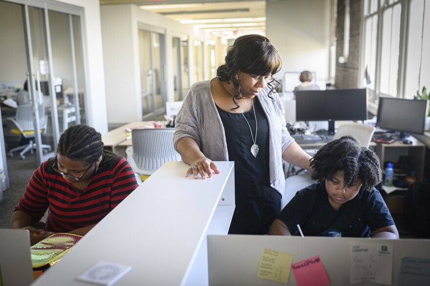 Ashana Bigard helps her children, Aiden Marie Bigard-Sallier (left), 13, and Brenton Bigard-Sallier, 8, with their homework after school at her office in New Orleans. Bigard is opposed to school closures, saying they are destabilizing and even traumatizing for students.