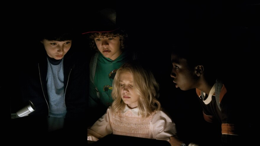 A mysterious young girl (Millie Bobby Brown) helps three boys (Finn Wolfhard, Gaten Matarazzo, Caleb McLaughlin) look for their missing friend in Netflix's <em>Stranger Things.</em>