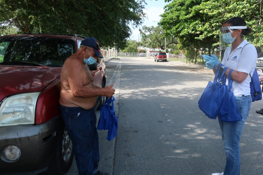Kathy Burgos, right, gives a bag of masks and resources to an Allapattah resident.