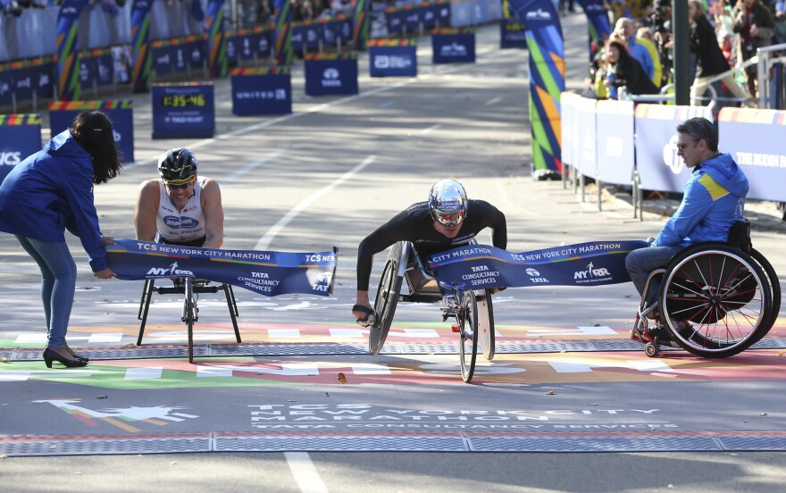 Marcel Hug of Switzerland, right, crosses the finish line first, just ahead of Kurt Fearnley of Australia, in the men's wheelchair division of the 2016 New York City Marathon on Sunday.