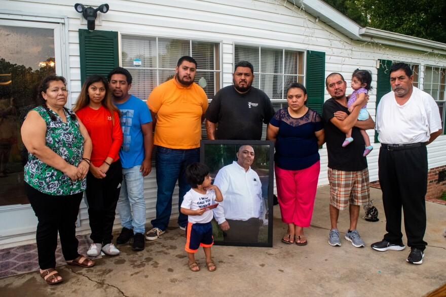Part of the Chagoyan family outside their home holding Juan's portrait