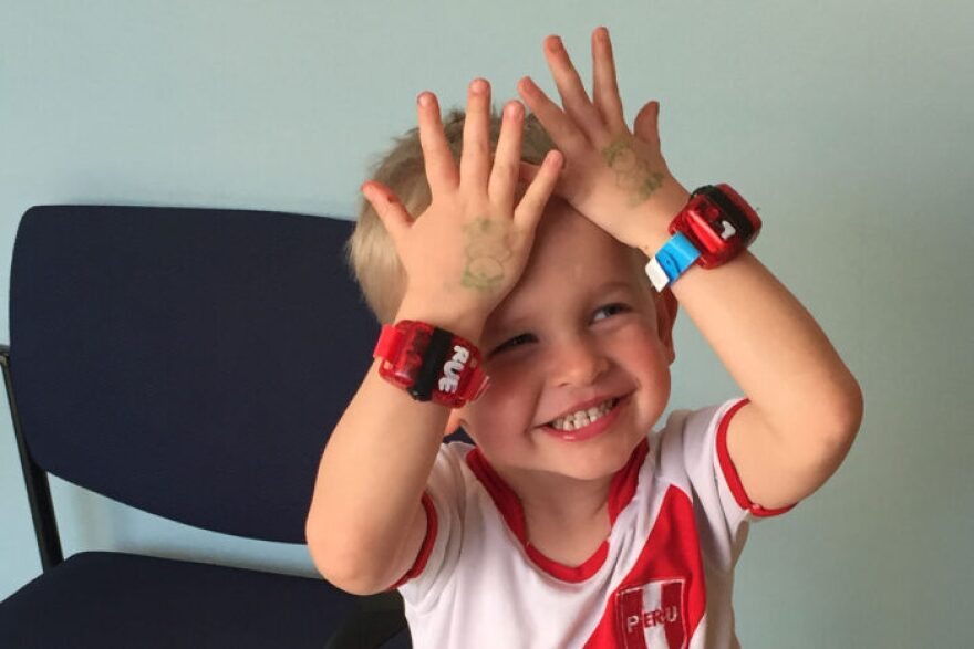 Noah Drozda shows off a pair of biosensors that he wore around the clock for a study on motor deficits in children.