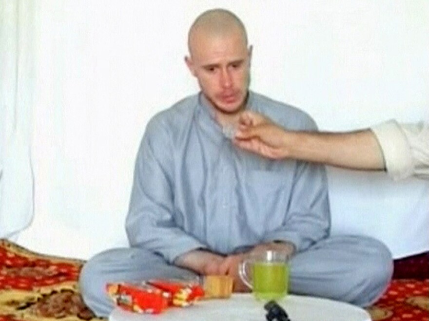 U.S. Army Sgt. Bowe Bergdahl watches as one of his captors displays his identity tag in the first of several videos of the soldier, in July, 2009.
