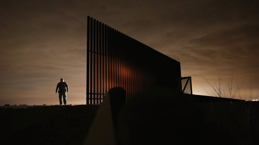 Border Patrol agent Sal De Leon stands near a section of the U.S.-Mexico border fence while on patrol last year in La Joya, Texas.