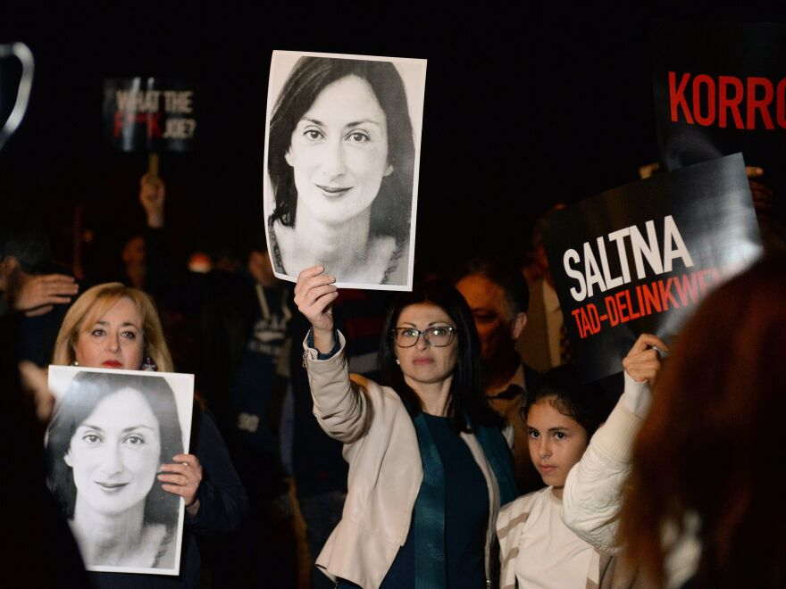 Protesters hold up pictures of Daphne Caruana Galizia as they gather earlier this month outside the prime minister's office in Valletta, Malta. Painful questions about the investigative journalist's murder have lingered since she was killed by a car bomb in 2017.