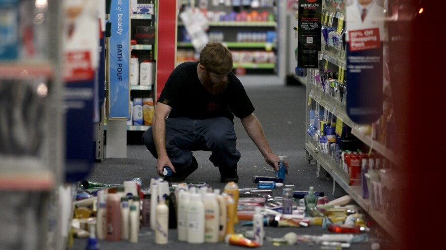 A man picks up fallen goods at a CVS store after an earthquake hit Friday near La Mirada, Calif. The magnitude-5.1 earthquake was widely felt in the Los Angeles area and surrounding counties.