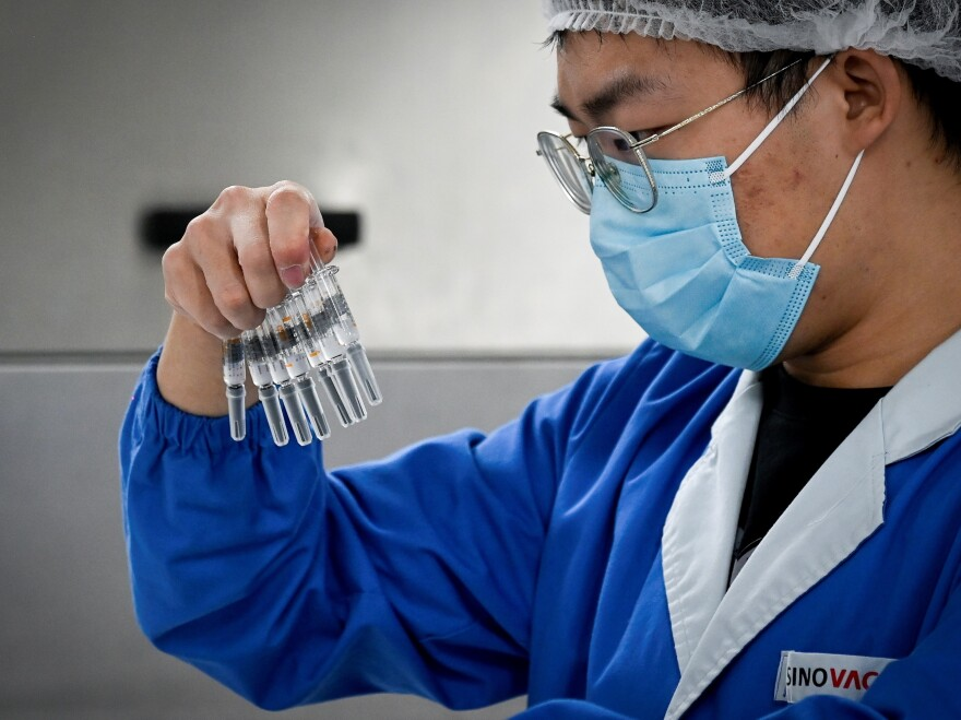 A staff member checks vaccines at a Beijing factory built by Sinovac to produce a COVID-19 coronavirus vaccine. Sinovac is one of 11 Chinese companies approved to carry out clinical trials of potential vaccines.