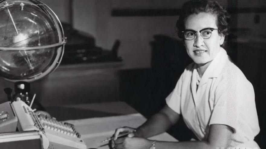 "Johnson at her desk at NASA Langley Research Center with a globe, or ""Celestial Training Device."""