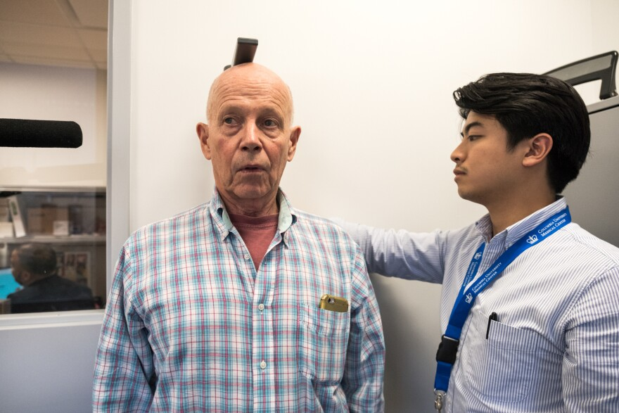 Steve Halliwell (left), a volunteer in the study, has his height measured for a second time by Dan Nguyen, a research assistant involved in the All of Us research initiative.