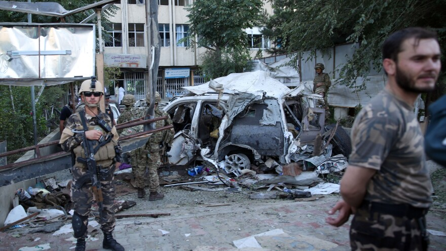 Afghan security forces and British soldiers inspect the site of a suicide attack in the heart of Kabul, Afghanistan, on Saturday. Three American civilian contractors are reportedly among the dead.