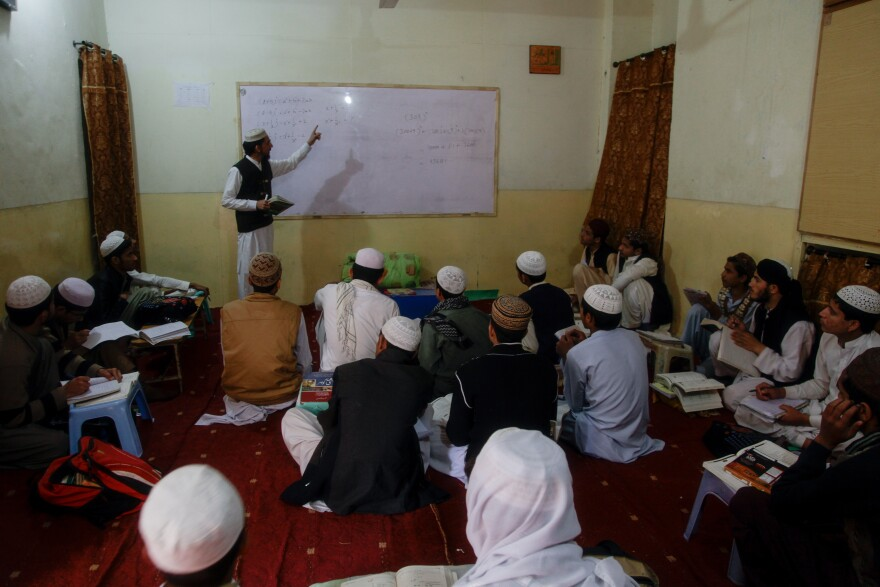 A teacher gives an algebra lesson during a math class at the Jamia Muhammadia madrassa.