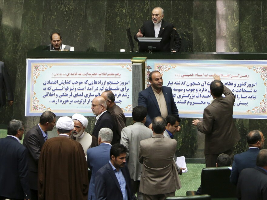 Ali Akbar Salehi, top, the head of Iran's Atomic Energy Organization, delivers a speech as lawmakers and officials discuss a bill on Iran's nuclear deal in parliament on Sunday. The parliament approved an outline of a bill allowing the deal's implementation.